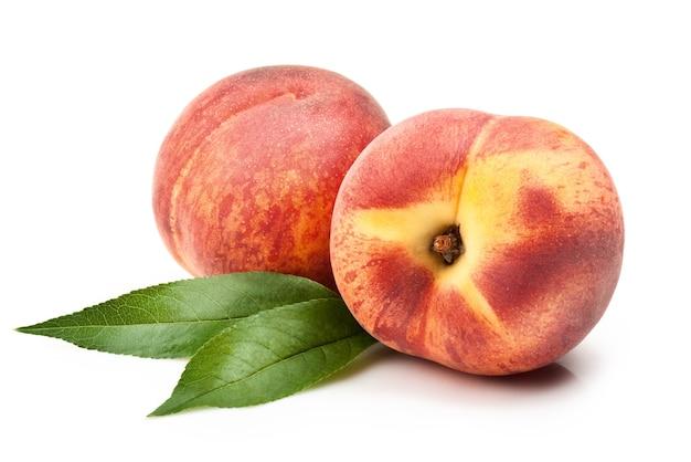 Dojrzałe owoce brzoskwini z liśćmi na białym tle