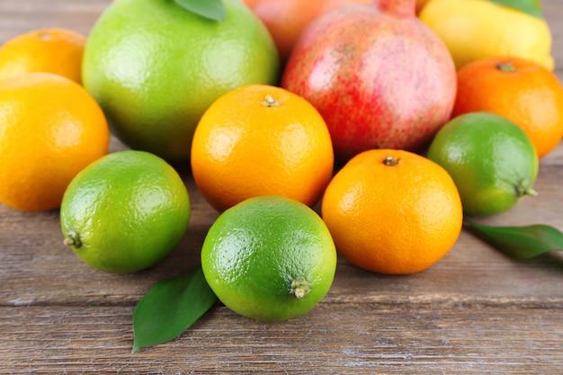Dojrzałe owoce cytrusowe z zielonymi liśćmi na podłoże drewniane