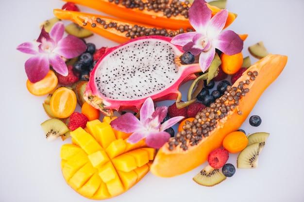 Dojrzałe owoce dargon, papaja, kiwi, mango z kumkwatem, ozdobione pięknymi orchideami.