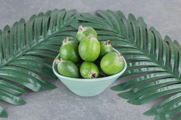 Dojrzałe owoce feijoa w niebieskiej misce z liśćmi. zdjęcie wysokiej jakości