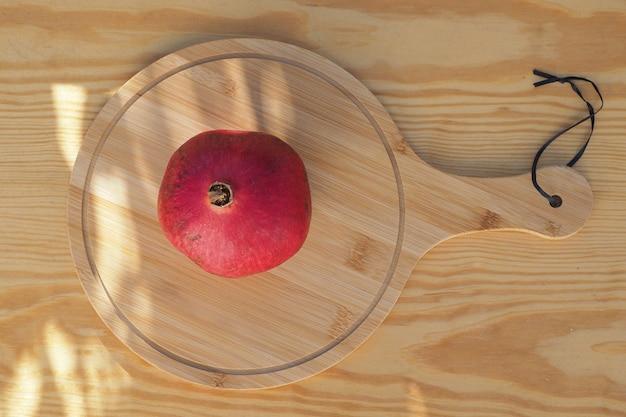 Dojrzałe owoce granatu na podłoże drewniane. widok z góry.
