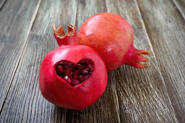 Dojrzałe owoce granatu z bliska na drewniane tła. koncepcja zdrowego odżywiania. wycięty w kształcie serca na skórce granatu.