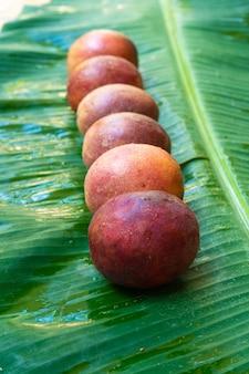Dojrzałe owoce męczennicy na mokrym liściu bananowca.