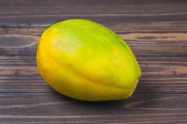 Dojrzałe owoce papai leżą na tle drewnianych desek