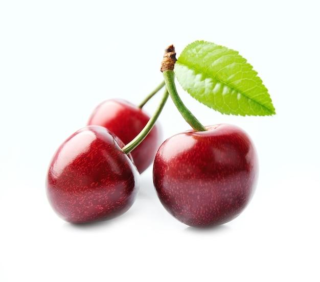 Dojrzałe owoce wiśni z liśćmi na białym tle.