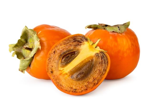 Dojrzałe persimmon i pół z bliska kości na białym tle. odosobniony.