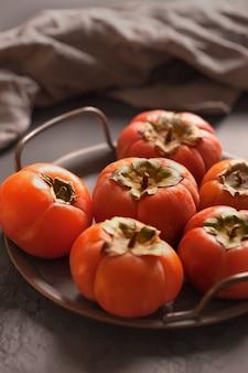 Dojrzałe persimmons na ciemnym talerzu