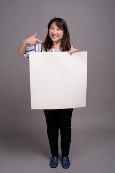 Dojrzałe piękne azjatyckie bizneswoman gospodarstwa pusty znak