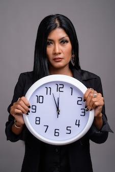 Dojrzałe piękne azjatyckie bizneswoman na szarym tle