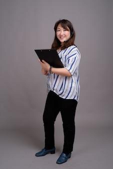 Dojrzałe piękne azjatyckie bizneswoman noszenie słuchawek i trzymając folder