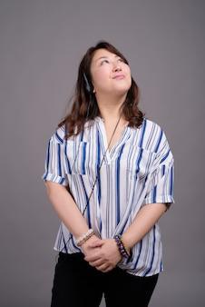 Dojrzałe piękne azjatyckie bizneswoman patrząc w górę