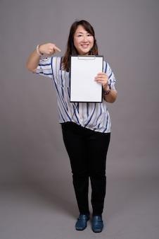 Dojrzałe piękne azjatyckie bizneswoman wskazując na pusty folder
