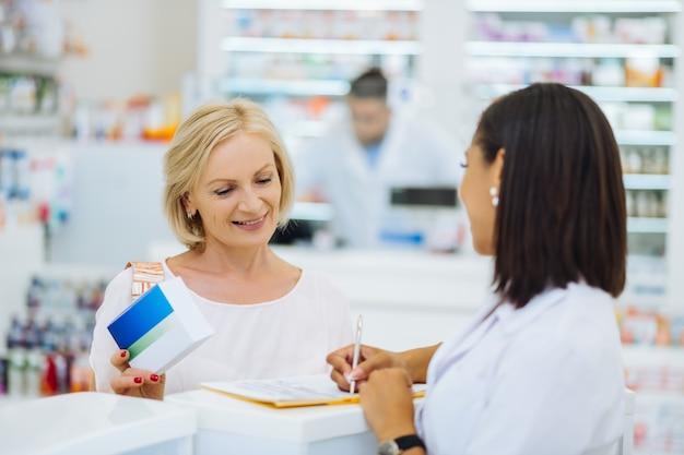 Dojrzałe piękno. uważna brunetka aptekarz stoi w swoim miejscu pracy i słucha swojego klienta