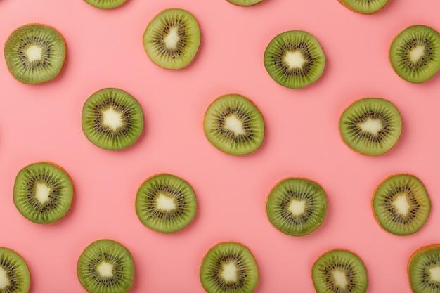 Dojrzałe plasterki kiwi we wzorach na różowym tle.