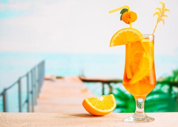 Dojrzałe plastry pomarańczy i kieliszek apetycznego soczystego napoju cytrusowego