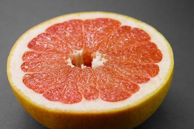 Dojrzałe pół owoców cytrusowych różowy grejpfrut na białym tle na szarym tle