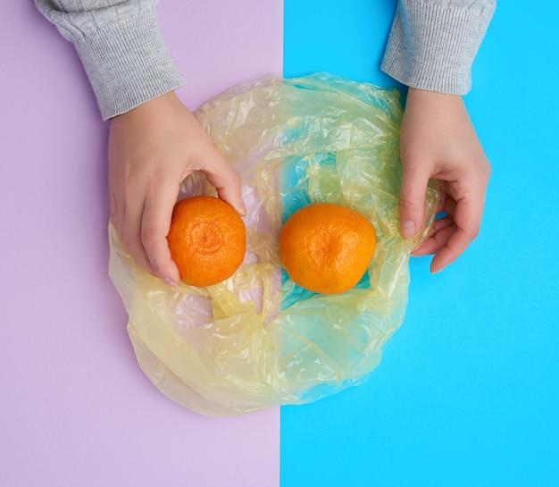 Dojrzałe pomarańczowe mandarynki leżą w przezroczystej plastikowej torbie