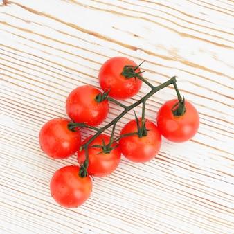 Dojrzałe pomidory czereśniowe na gałązce na białym drewnianym bliska