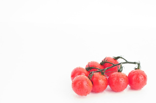 Dojrzałe pomidory czereśniowe na gałązce na białym tle - obraz