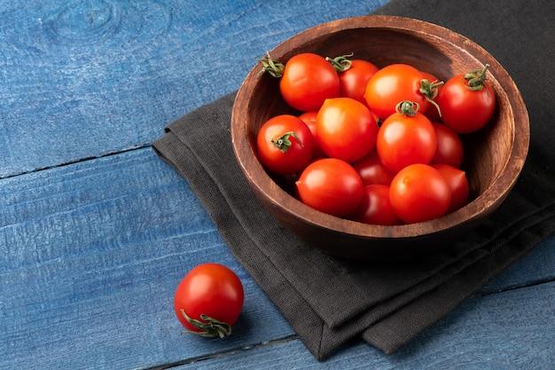 Dojrzałe pomidory czereśniowe w drewnianej tablicy na niebieskim tle