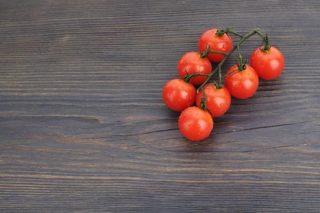 Dojrzałe pomidory koktajlowe na gałązce na ciemnym drewnianym