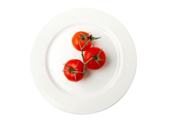 Dojrzałe pomidory na gałęzi na białym talerzu. wegetarianizm, dieta zdrowa żywność i witaminy z natury. zbliżenie. widok z góry. na białym tle.
