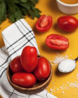 Dojrzałe pomidory śliwkowe na drewnianym talerzu sól w łyżce i świeża rukola