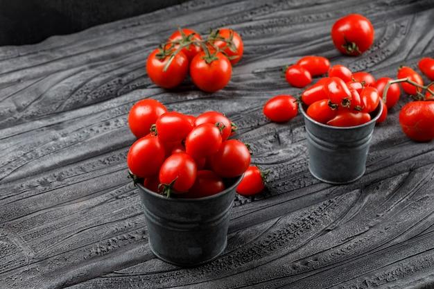 Dojrzałe pomidory w mini wiadrach na szarej drewnianej i czarnej ścianie. wysoki kąt widzenia.