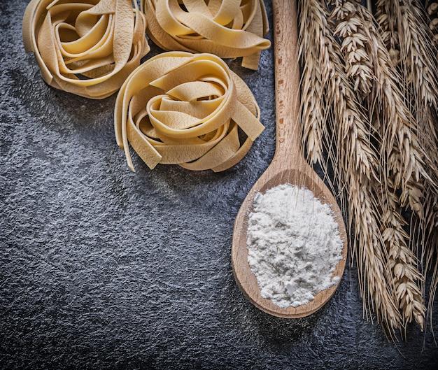 Dojrzałe pszenne kłosy żytnie, drewniana łyżka, mąka i niegotowany makaron na czarnej powierzchni