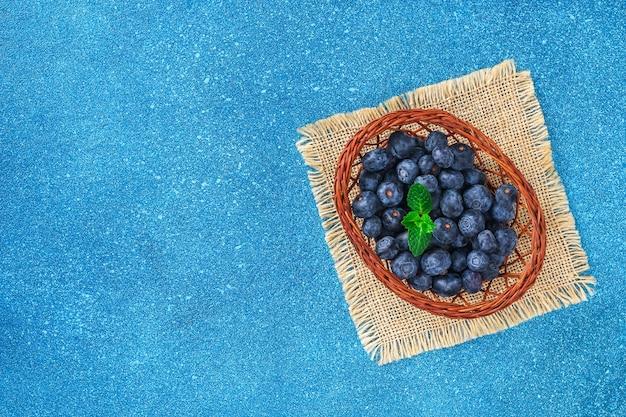 Dojrzałe pyszne czarne jagody w drewnianym koszu