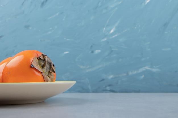 Dojrzałe pyszne persimmons na żółtym talerzu.
