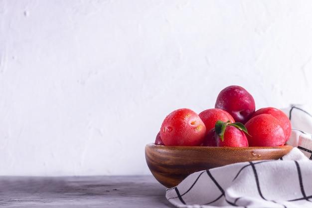 Dojrzałe śliwki w drewnianym talerzu z rosą z chusteczką