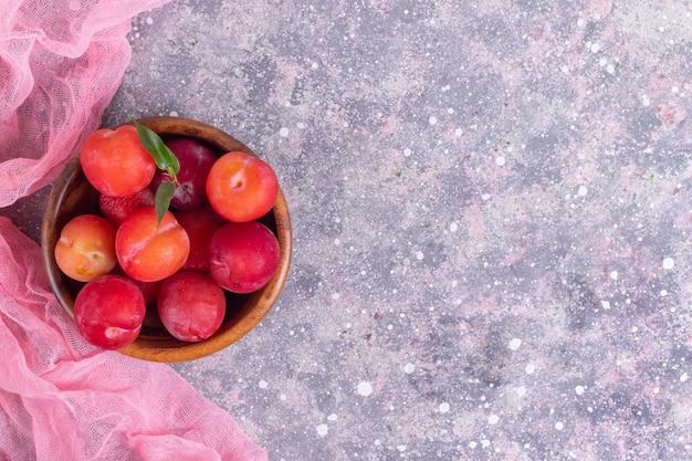 Dojrzałe śliwki w drewnianym talerzu z rosą z różową serwetką