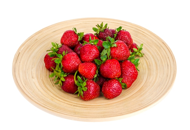 Dojrzałe słodkie średniorolne czerwone truskawki na drewnianym naczyniu