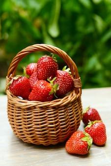 Dojrzałe słodkie truskawki w wiklinowym koszu na stole w ogrodzie