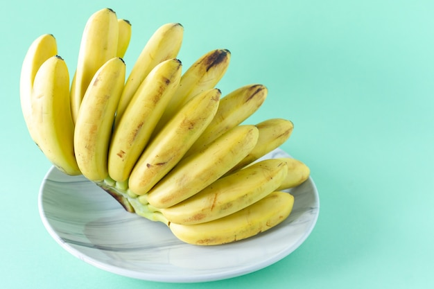 Dojrzałe smaczne banany na talerzu na niebieskim tle. koncepcja zdrowego jedzenia.