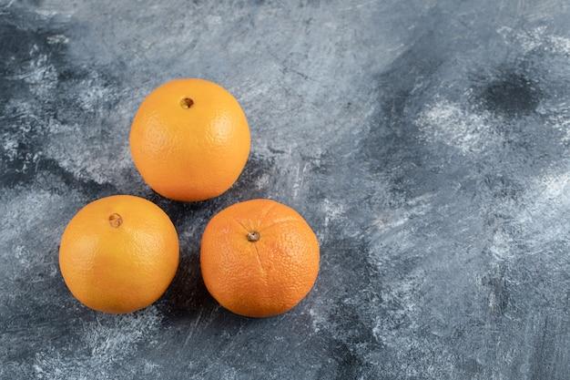Dojrzałe smaczne pomarańcze na marmurowym stole.