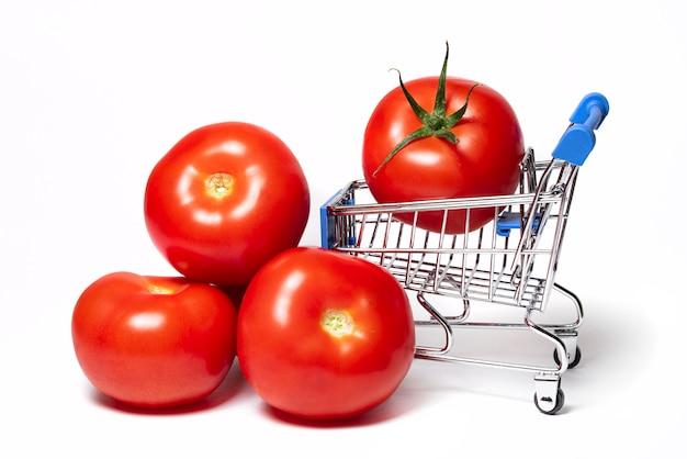 Dojrzałe soczyste czerwone pomidory z wózkiem spożywczym jesienne zbiory wózek sklepowy z produktami spożywczymi