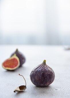 Dojrzałe, soczyste figi leżą na białym stole w pobliżu okna. poranne światło. zamknij i skopiuj miejsce