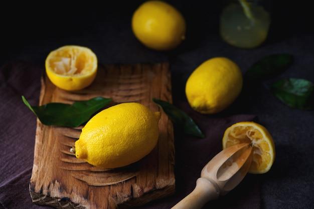 Dojrzałe, soczyste, organiczne cytryny na desce, ciemnym tle