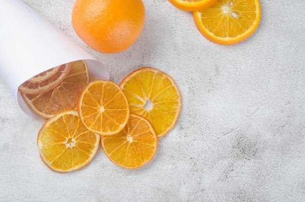 Dojrzałe soczyste pomarańcze na szarym tle i suszone chipsy pomarańczy wokół. chipsy owocowe. koncepcja zdrowego odżywiania, przekąska, bez cukru. widok z góry, kopia przestrzeń.