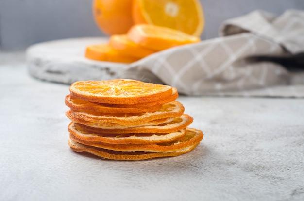 Dojrzałe soczyste pomarańcze na szarym tle i suszone chipsy pomarańczy wokół. chipsy owocowe.