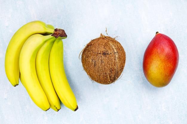 Dojrzałe, soczyste, tropikalne lato, owoce sezonowe, mango, kokos, kiwi, banany, truskawki, na żółtym tle.
