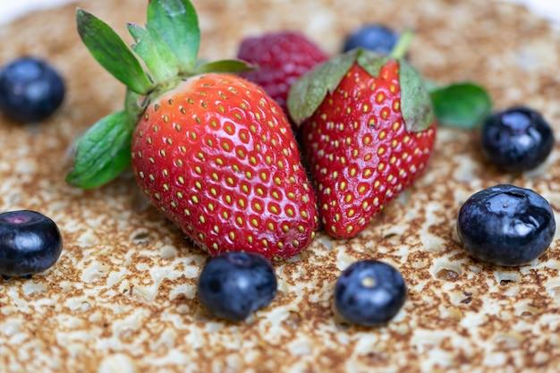 Dojrzałe, soczyste truskawki i jagody leżą na pysznym naleśniku. danie narodowe kuchni rosyjskiej bliny ze świeżymi jagodami.
