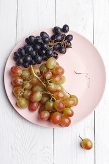Dojrzałe soczyste winogrona na talerzu na białym drewnie. widok z góry.