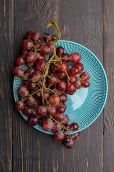 Dojrzałe soczyste winogrona na talerzu na ciemnym drewnie. widok z góry.
