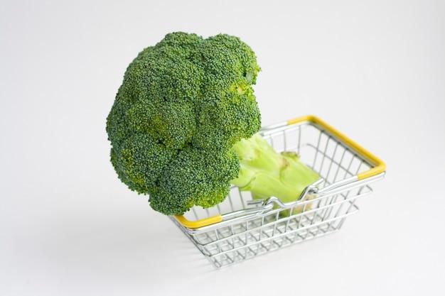 Dojrzałe surowe brokuły w koszyku na białym tle