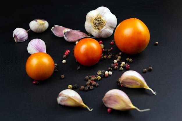 Dojrzałe surowe pomidory, czosnek na czarnym tle.