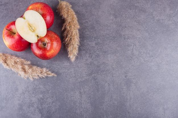 Dojrzałe, świeże, czerwone jabłka umieszczone na kamiennym tle.