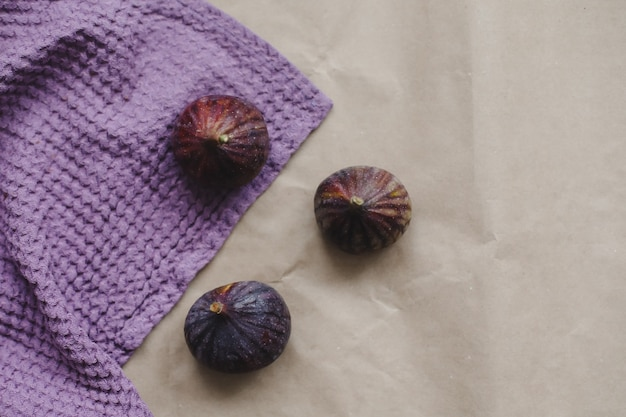 Dojrzałe świeże figi i fioletowe tkaniny na rustykalnym tle płaski widok z góry